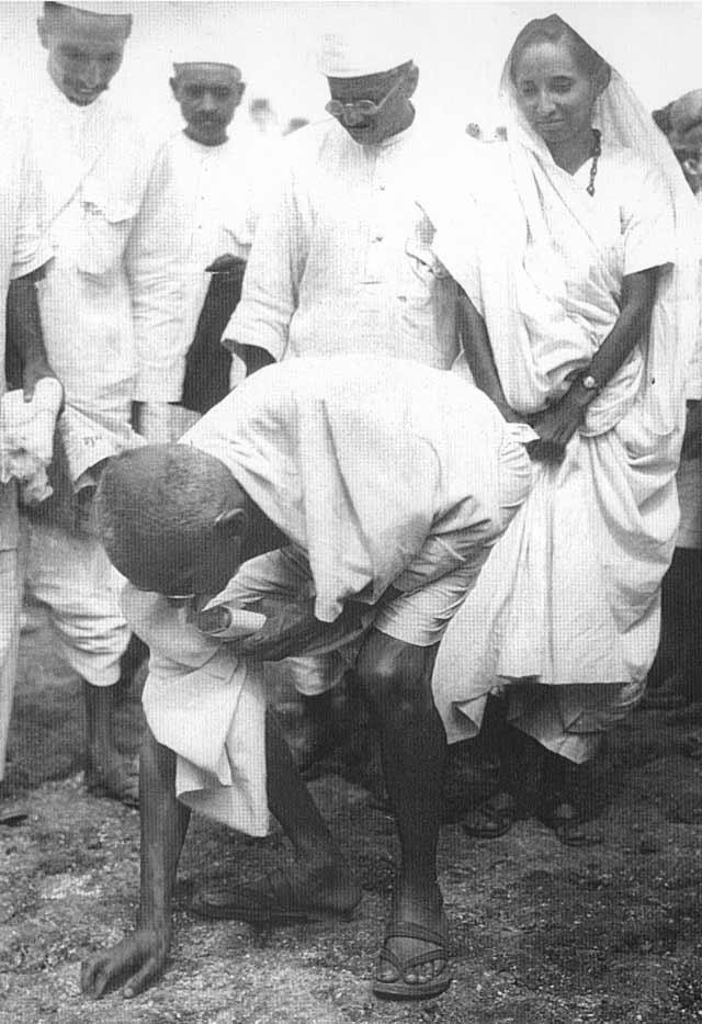 Gandhi à Dandi, le 5 avril 1930, ramassant une poignée de boue salée