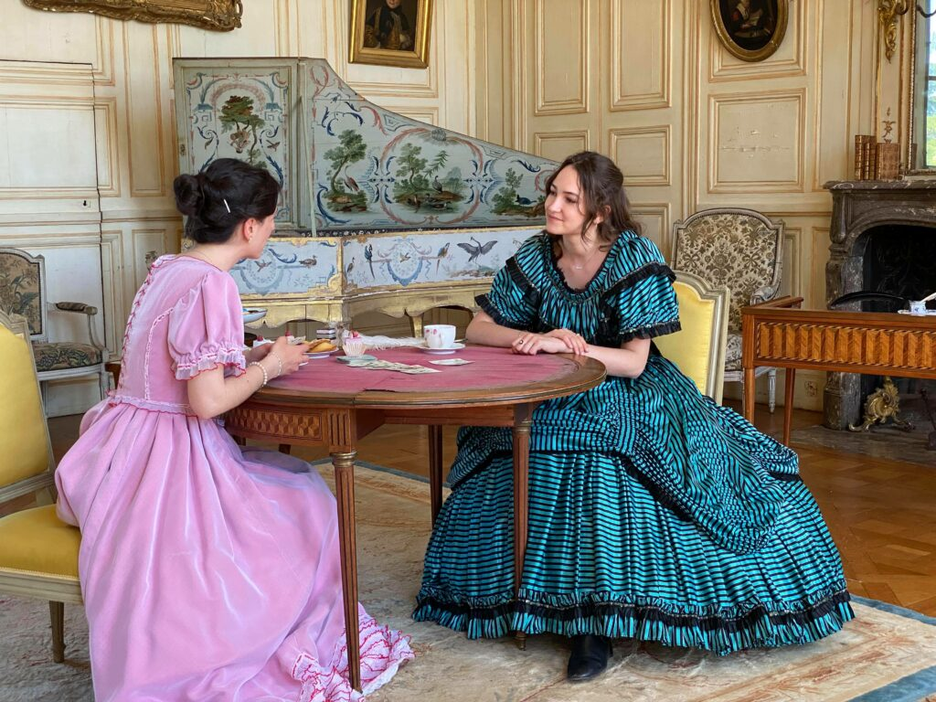 Deux femmes vêtues des robes d'époque, assises à la table. Une porte une robe rose, l'autre aqua marine aux rayures.