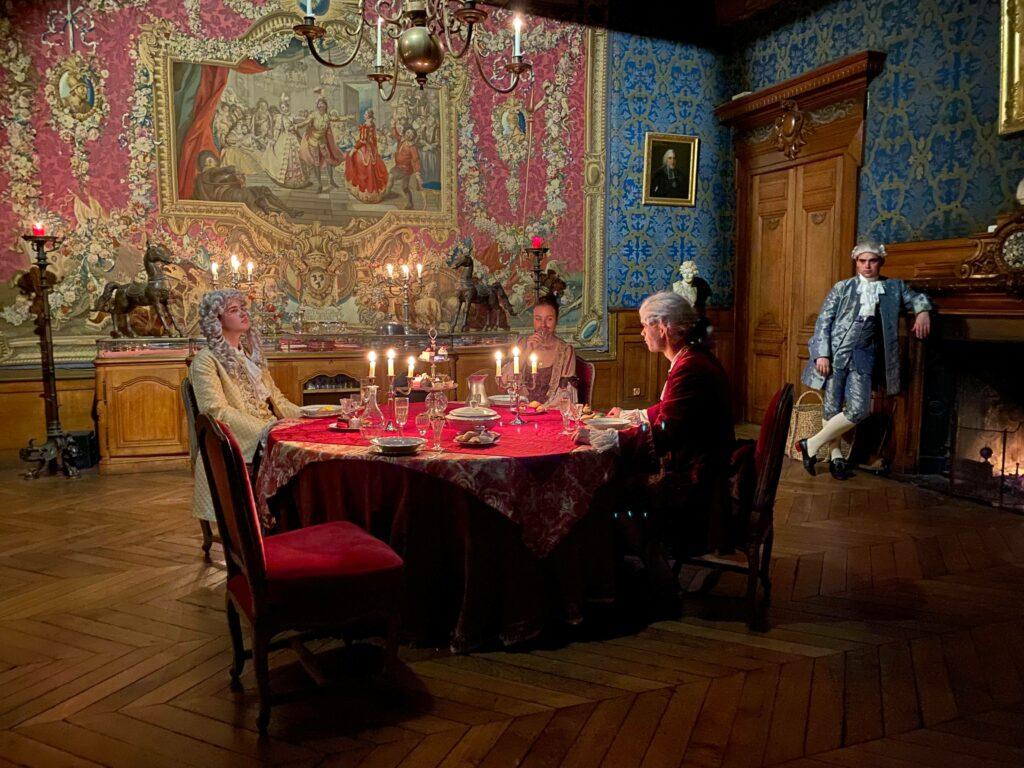 Un diner dans une chambre du château très richement ornée ; 3 personnes assises à la table, en train de dîner, un homme à côté s'accoude à la cheminée. Tous vêtus de costumes d'époque.