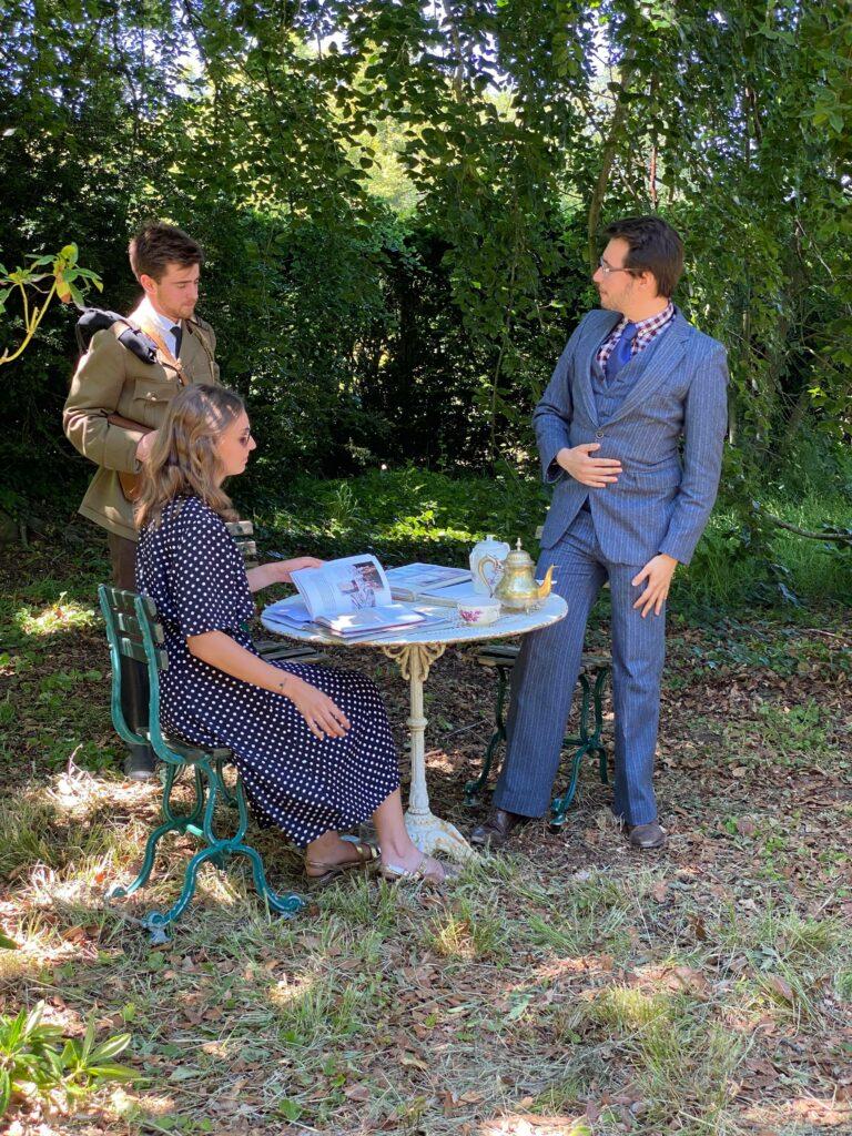 Trois personnes dans un jardin ; deux sont assises à la table sur laquelle est posée une bouilloire et deux livres. A côté, un soldat dans un uniforme de Seconde Guerre Mondiale.